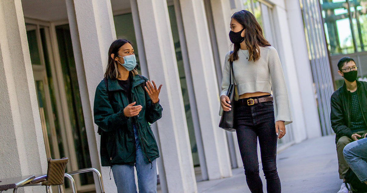 Two UBC students walking and talking outdoors, wearing masks during the COVID-19 pandemic.